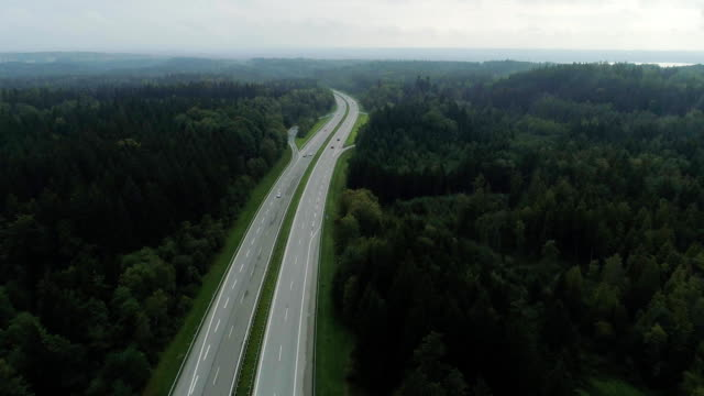 Cars on the Autobahn in Germany fast driving beautiful road A fast road in the forest and in the field on which fast cars without speed limit go autobahn stock videos & royalty-free footage