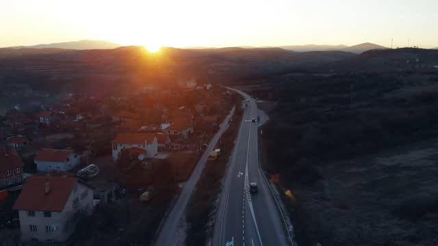 Cars pass the regional highway into the golden winter sunset - Transport