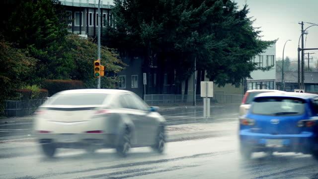 auto passa sotto la pioggia sulla giornata nuvolosa - passare davanti video stock e b–roll