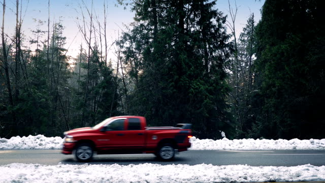 Cars Passing On Snowy Road Through Forest video