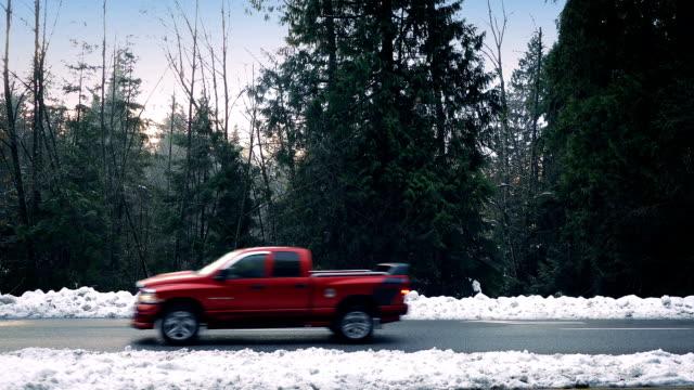autos fahren auf schneefall durch wald - seitenansicht stock-videos und b-roll-filmmaterial