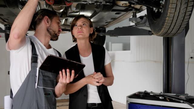 vídeos de stock e filmes b-roll de car's service worker talk with customer, master shows technical condition car on tablet, auto repairman shows on breakdown - fundo oficina