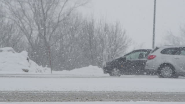 SLOW MOTION: Cars slowly drive up and down a slippery road during a snowstorm.