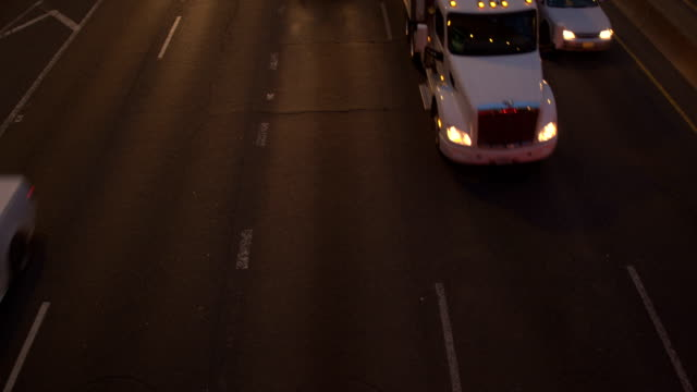 SLOW MOTION Cars, SUV, semi truck driving on busy multiple lane highway by night