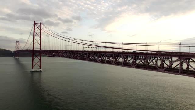 cars, trains, bus on 25 april bridge in lisbon aerial view - lisbona video stock e b–roll