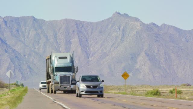 stockvideo's en b-roll-footage met auto's, vrachtwagens, semi-vrachtwagens en andere voertuigen rijden over een snelweg met bergen op de achtergrond in arizona op een zonnige dag - arizona highway signs