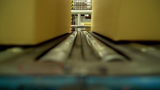 Carton box moving on conveyor rollers.