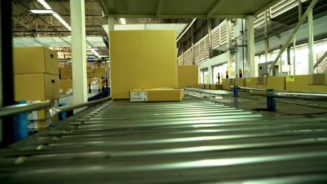 carton box moving on conveyor rollers. - packaging video stock e b–roll