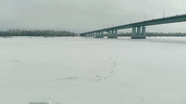 carved ice cross on white frozen river with huge gray bridge