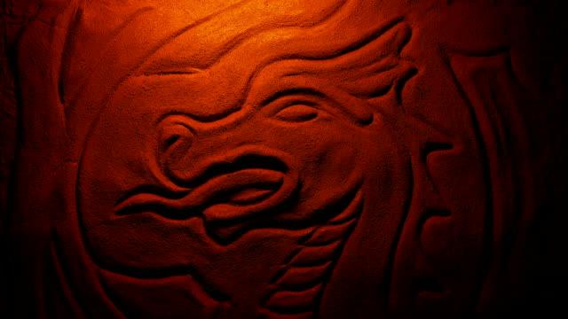carved stone dragon in fire glow - smok postać fikcyjna filmów i materiałów b-roll