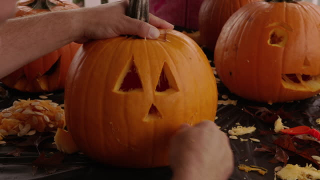 carving jack o lantern pumpkin for halloween - pumpkin стоковые видео и кадры b-roll