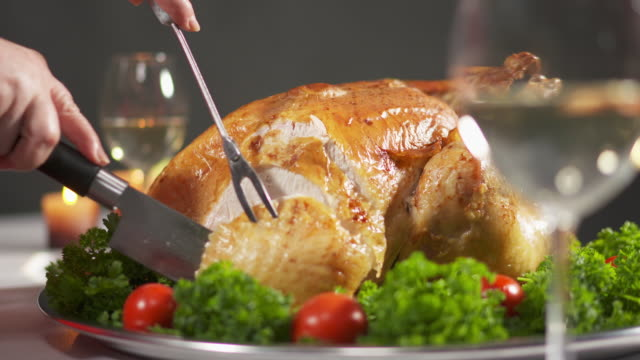 Carving the turkey in slow motion cutting juicy breast meat.