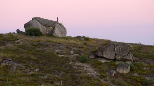 vídeos de stock e filmes b-roll de casa do penedo boulder house in fafe, portugal at sunset - isolated house, exterior