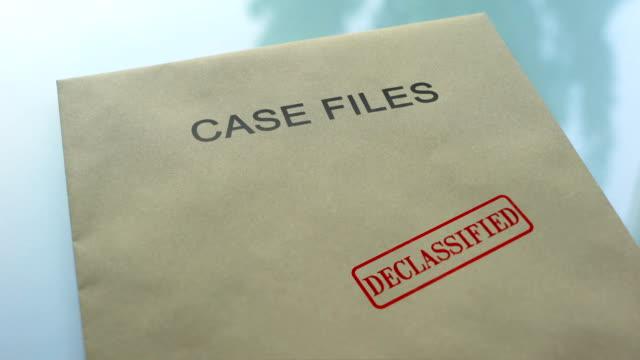 機密解除されたファイルの場合、重要な書類をフォルダーにシールをスタンプを手 - クラシファイド広告点の映像素材/bロール