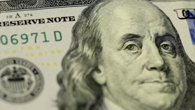 Cash money background. Benjamin Franklin portrait on 100 US dollar bill close up, the image is rotated video