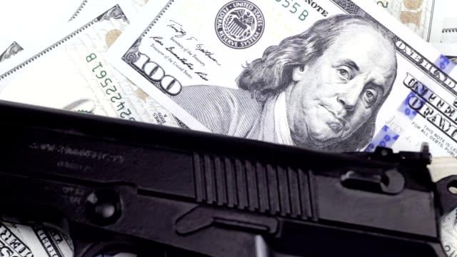 vídeos de stock e filmes b-roll de cash one hundred dollar bills under the gun, rotating background - roubar crime