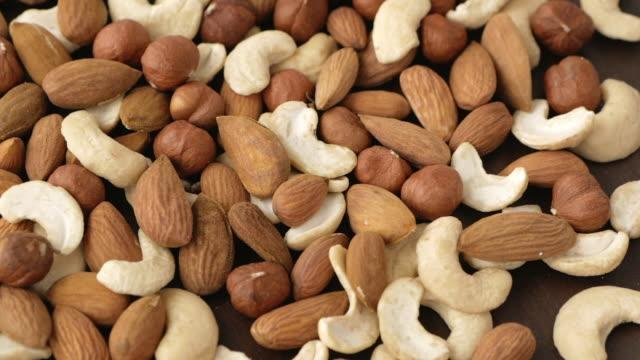 vídeos de stock e filmes b-roll de cashews, almonds and hazelnuts rotating - frutos secos