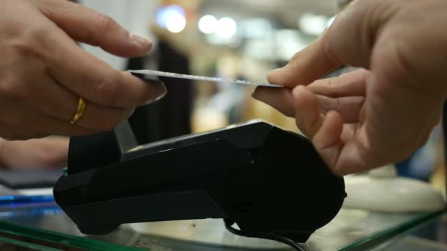 vídeos de stock, filmes e b-roll de caixa utilizando o leitor de cartão de crédito - boutique