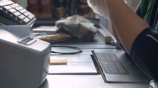 руки кассира в защитных перчатках - касса стоковые видео и кадры b-roll