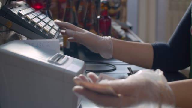 cashier's hands in protective gloves - essential workers stock videos & royalty-free footage