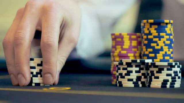 Casino: Man playing poker, excited, turns casino tokens in hand. Close up, video