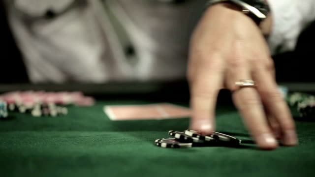 Casino: Man playing poker, excited, turns casino tokens in hand video