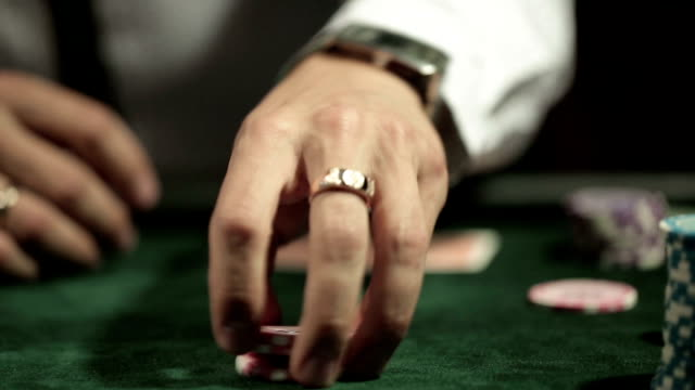 Casino: Man playing poker, tokens in hand. Close up video