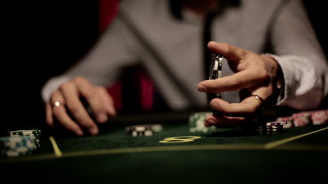 Casino, poker: Player shuffles chips famously. Close up video