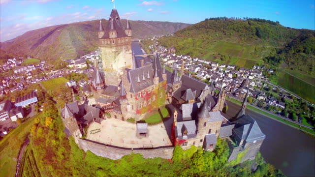 vídeos de stock e filmes b-roll de castle aerial shot, beautiful walls roof tops of medieval fortress on mosel river in germany, beauty tourist attraction and family vacation in summer. ancient castle with vine hills fly over - castle
