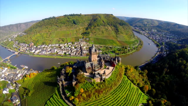 Castle on river island, medieval landscape, aerial, ships bridge. Beautiful aerial shot above Europe, culture and landscapes, camera pan dolly in the air. Drone flying above European land. Traveling sightseeing, tourist views of Germany. video
