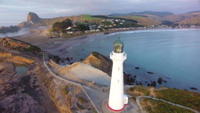vídeos de stock e filmes b-roll de castlepoint lighthouse with castlepoint village in background. - wellington