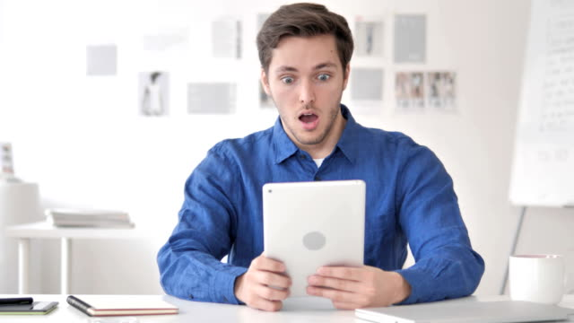 Casual Adult Man in Shock while Using Tablet