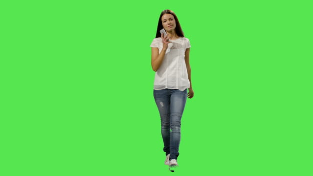 vídeos de stock e filmes b-roll de casual brunette woman is walking and talking on the phone on a mock-up green screen in the background. - teeshirt template