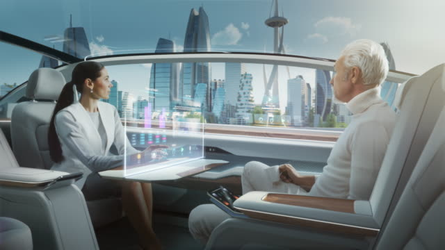 vídeos de stock e filmes b-roll de casual business meeting between senior male and female inside a futuristic driverless autonomous car with augmented reality presentation interface. self-driving van driving on downtown city streets. - business woman hologram