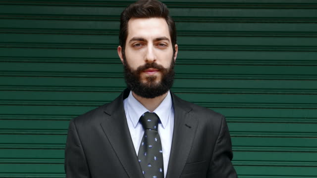 Casual businessman looking at camera Casual stylish businessman with beard and mustaches looking at camera. beard stock videos & royalty-free footage