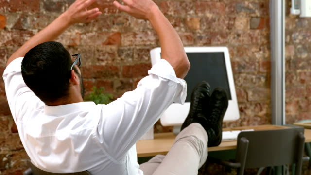 Casual businessman relaxing at desk leaning back video