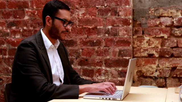 stockvideo's en b-roll-footage met casual businessman typing at his desk - mid volwassen mannen