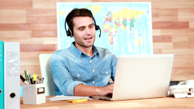 Casual businessman using laptop and having conversation with headset video