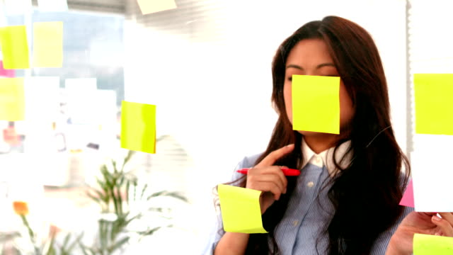 Casual businesswoman writing on post it video