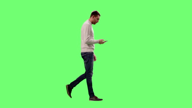 Casual Caucasian Man is Walking and Talking on the Phone on a Mock-up Green Screen in the Background.