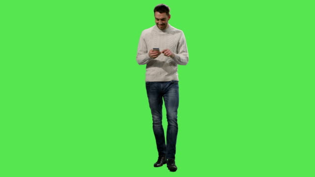 Casual caucasian man is walking and using smartphone on a mock-up green screen in the background. Casual caucasian man is walking and using smartphone on a mock-up green screen in the background. Shot on RED Cinema Camera in 4K (UHD). front view stock videos & royalty-free footage