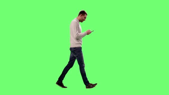 vídeos de stock, filmes e b-roll de homem caucasiano casual é curta e usando o smartphone em uma tela verde de mock-up em segundo plano. - fundo verde