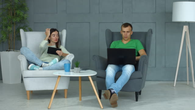 Casual couple networking with digital devices at home Attractive couple with digital devices networking and chatting while sitting in armchairs in modern interior. Positive couple spending leisure browsing social media using tablet and laptop at home. lounge chair stock videos & royalty-free footage