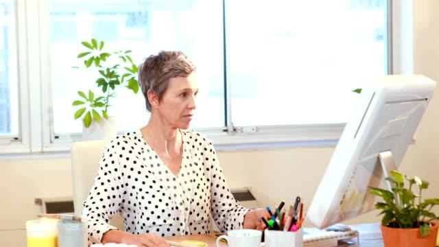 casual female designer working in office - mature women studio grey hair bildbanksvideor och videomaterial från bakom kulisserna