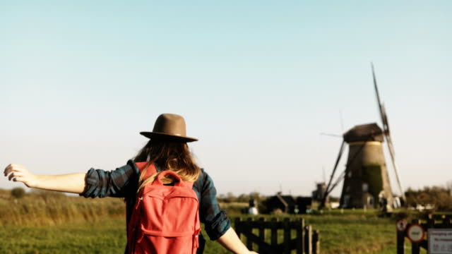 Casual girl jumps over fence near windmill farm. Woman in hat with long hair and red backpack returns home on sunset. 4K