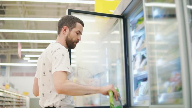 Casual guy buys food in store. Handsome man taking frozen food from shelves in a fridge of a grocery store. Man with a tattoo shopping for food, buying groceries in supermarket. frozen stock videos & royalty-free footage