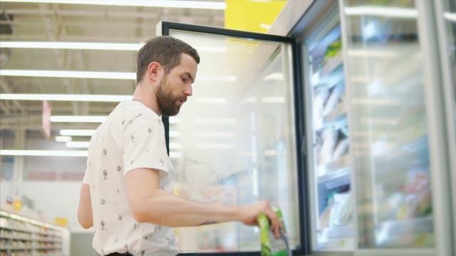 casual guy buys food in store. - замороженные продукты стоковые видео и кадры b-roll