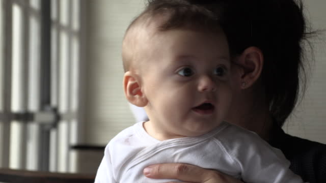 casual infant baby being held by mom looking to camera - 0 11 mesi video stock e b–roll