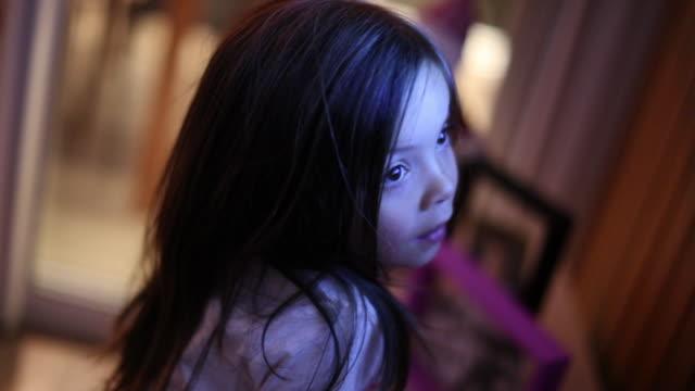 vídeos de stock e filmes b-roll de casual little girl watching tv screen at night. small child staring at screen - tv e familia e ecrã