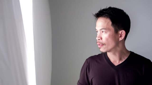 vídeos de stock, filmes e b-roll de homem casual, beber um café ao lado da janela - camiseta preta